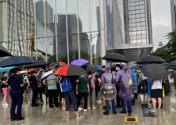 헝다그룹 때문에 손해를 입은 투자자와 상품 구매자들이 14일(현지시간) 비가 내리는 속에서도 중국 광둥성 선전의 헝다그룹 본사 앞에서 시위를 하고 있다.   [이미지 출처= 블룸버그AFP]