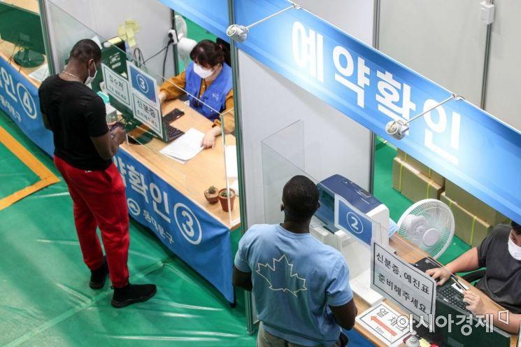 국민 70%가 코로나19 백신 1차 접종 달성을 앞두고 있는 16일 서울 동대문구체육관에 마련된 접종센터를 찾은 외국인들이 접수를 하고 있다./강진형 기자aymsdream@