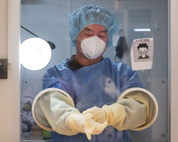 안철수 국민의당 대표가 18일 오전 서울 중구보건소 선별진료소에서 의료자원 봉사를 하기 위해 일회용 장갑을 끼고 있다. [이미지출처=연합뉴스]