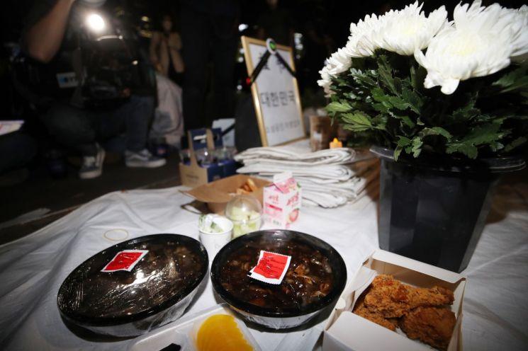 지난 16일 '코로나19 대응 전국자영업자비상대책위원회(자대위)'가 서울 국회의사당역 앞에 설치한 분향소에 국화와 음식 등이 놓여 있다. / 사진=연합뉴스