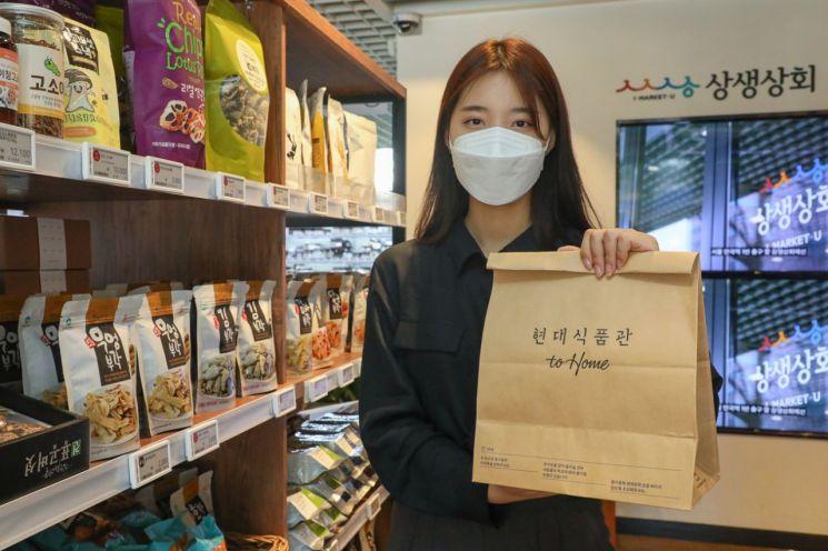 서울시 종로구 상생상회 매장에서 현대백화점 직원이 '현대식품관 투홈' 종이 쇼핑백을 들고 있다.