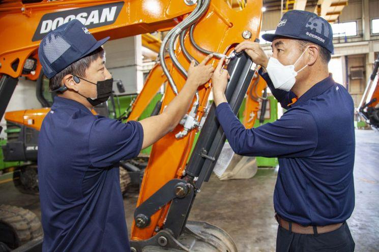 대한민국 명장 김주호 기술부장(오른쪽)이 현대두산인프라코어 인천공장에서 후배에게 기술을 전수하고 있다.(사진제공=현대두산인프라코어)