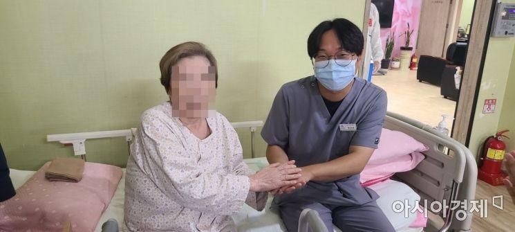 무연고 환자 A씨와 황명환 보건의료정보관리사가 지난달 31일 경기도 의정부 카네이션 요양병원 내 병상 침대에 앉아 함께 웃어보이고 있다.