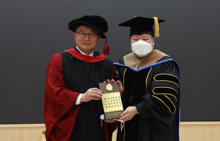 김충석 엔젤피스예술단 이사장(오른쪽)이 동명대 전호환 총장으로부터 '두잉총장' 제1호 명예박사 학위를 수여받았다.