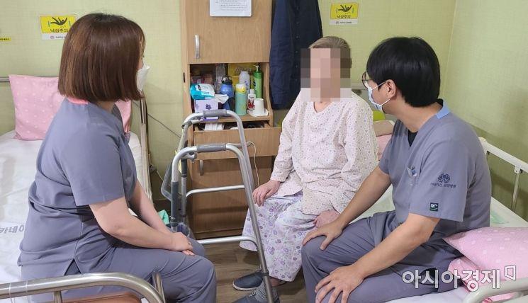 무연고 환자 A씨와 박윤식 사회복지사, 황명환 보건의료정보관리사가 지난달 31일 경기도 의정부 카네이션 요양병원 내 병상 침대에 앉아 함께 웃어보이고 있다.