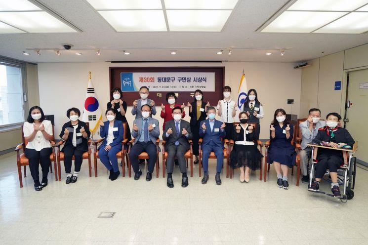 유덕열 동대문구청장(앞줄 가운데)과 14명의 구민상 수상자가   24일 동대문구청에서 열린 제30회 동대문구 구민상 시상식에서 기념촬영을 하고 있다