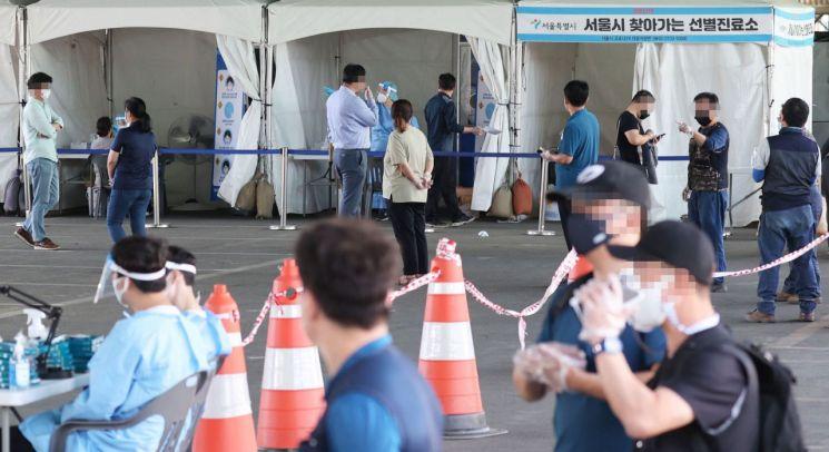 24일 서울 송파구 가락시장에 마련된 선별진료소에서 시민들이 코로나 19 검사를 위해 줄지어 서있다. [이미지출처=연합뉴스]