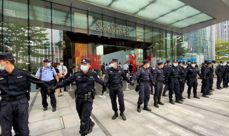 지난 13일 중국 선전의 헝다 본사 앞에서 채권 이자 지급을 요구하는 투자자들의 시위를 앞두고 공안 당국이 병력을 배치해 회사 주변을 통제하고 있다. [이미지출처=로이터연합뉴스]