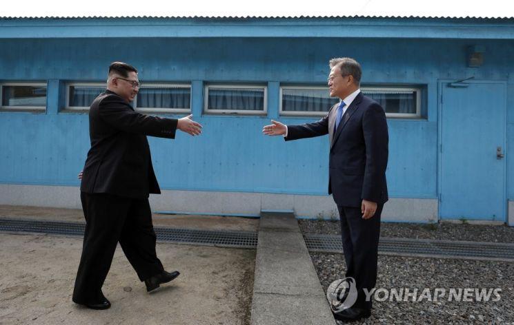 문재인 대통령과 김정은 북한 총비서가 2018년 4월 27일 판문점 군사분계선을 사이에 두고 악수하고 있다. [이미지출처=연합뉴스]