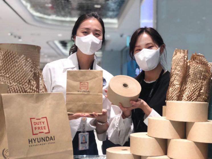 현대백화점면세점 인천공항점에서 직원들이 종이 포장재를 소개하고 있다.