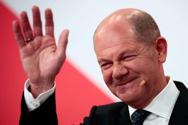 울라프 슐츠 독일 사회민주당(SPD) 총리 후보가 26일(현지시간) 연방의원 총선거 출구조사 결과 발표 직후 베를린 당사에서 당원들에게 손을 흔들며 미소짓고 있다. 베를린(독일)=로이터·연합뉴스