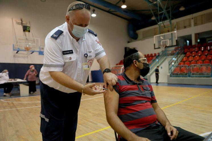 지난달 이스라엘 중부 홀론에서 한 남성이 공공의료진으로부터 코로나19 화이자 백신 3차 접종('부스터 샷')을 맞고 있다. [이미지출처=AFP연합뉴스]