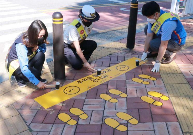 CJ대한통운이 경기도 군포시 어린이보호구역에 노란발자국을 설치하고 있다.
