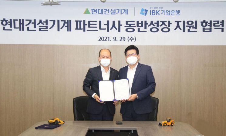 양경신 현대건설기계  구매본부장(오른쪽)과 박주용 IBK기업은행 부행장이 협력사 스마트 공장 지원 위한 업무협약(MOU)을 체결한 뒤 기념촬영하고 있다.[사진제공=현대제뉴인]