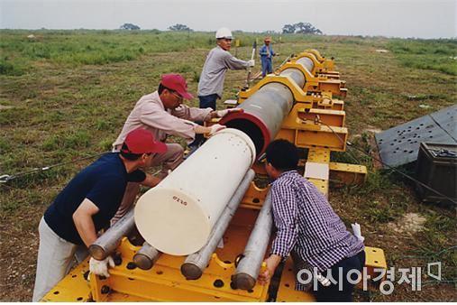 2001년 5월에 국방과학연구소 연구원들이 CMG에 직접 탄을 장착하는 모습. (사진제공=국방과학연구소)