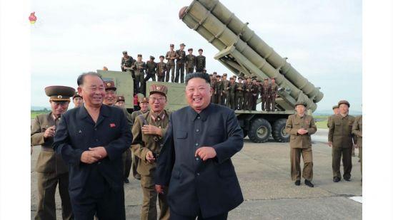 조선중앙TV가 지난 25일 오후 공개한 사진에서 김정은 국무위원장이 방사포를 뒤로 하고 활짝 웃는 모습. 김 위원장 뒤로 최근 북한 신무기 개발의 핵심으로 관측되는 전일호 군 상장이 따라오고 있다.