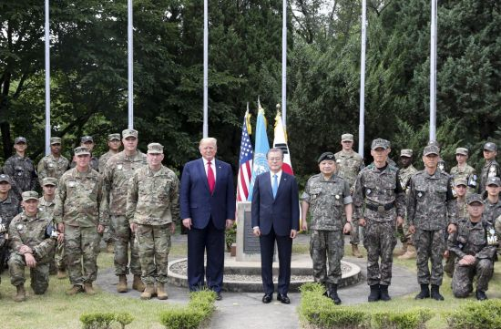 문재인 대통령과 트럼프 미국 대통령이 지난 6월30일 오후 비무장지대(DMZ) 내 미군 부대 캠프보니파스를 방문했다. 한미 정상이 유엔군 참전국 국기 게양대 앞에서 한-미 장병들과 기념촬영하고 있다. (사진=연합뉴스)